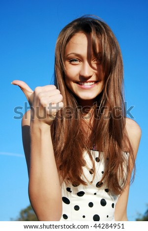 Closeup portrait of a beautiful young woman showing thumbs up sign