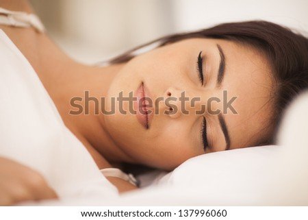 Closeup portrait of a beautiful young woman sleeping on the bed - stock photo