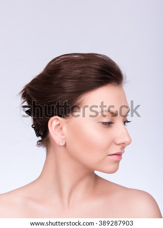 Closeup portrait of a beautiful young woman with collected hair and smooth skin. Profile, gaze directed downwards. Neutral grey background