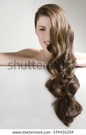 Closeup portrait of a beautiful young woman with long curly brown hair against gray background - stock photo