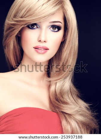 Closeup portrait of a beautiful young woman with long white hairs. Fashion model posing at studio
