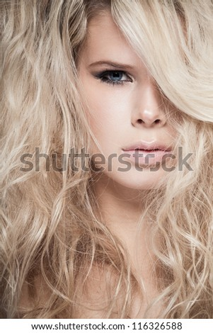 Closeup portrait of a blond lady with hair over her face - stock photo