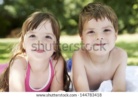 Closeup portrait of a boy and girl lying in the backyard - stock photo