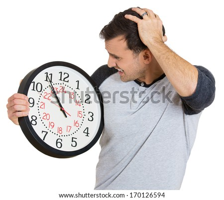 Closeup portrait of a business man, student, leader holding a clock very stressed, pressured by lack of and running out of time late for a meeting, isolated on a white background. Negative emotions