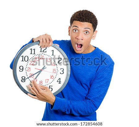 Closeup portrait of a business man, student, leader holding a clock very stressed, pressured by lack of and running out of time late for a meeting, isolated on a white background. Negative emotions - stock photo