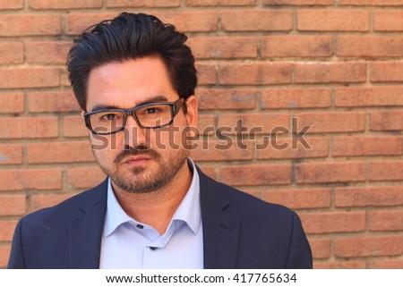 Closeup portrait of a businessman against brick wall background - stock photo
