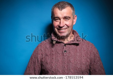 closeup portrait of a casual middle aged man smiling for the camera. on a blue vignetted background  - stock photo