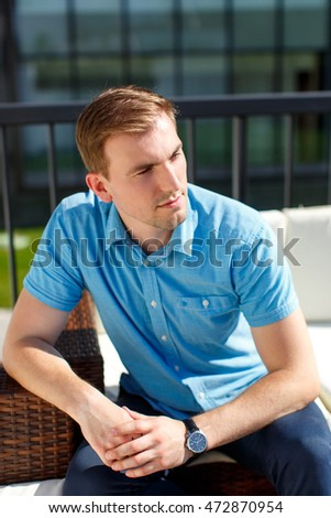 closeup portrait of a casual young man sitting on sofa and looking away from the camera to his side, with a serious look on his face.