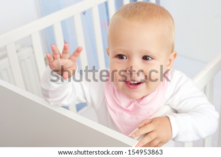 Closeup portrait of a cheerful baby waving hello