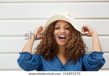 Closeup portrait of a cheerful young woman with hat laughing outdoors - stock photo