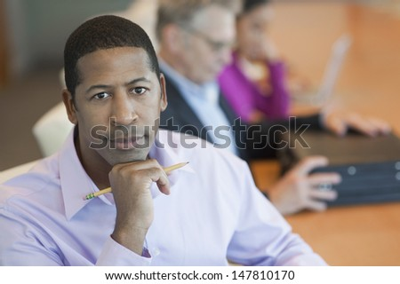 Closeup portrait of a confident businessman with blurred multiethnic colleagues in background - stock photo