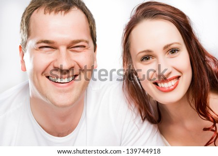 closeup portrait of a couple, smiling and looking into the camera - stock photo