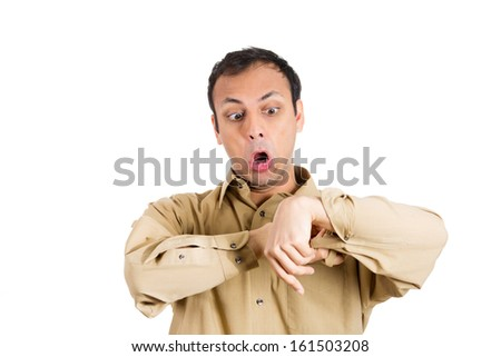 Closeup portrait of a crazy looking young man in yellow, brown shirt, staring with shock and surprise at his wrist, as there is something there, isolated on white background. Human facial expressions - stock photo