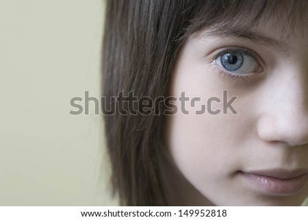 Closeup portrait of a cropped blue eyed girl with brown hair against colored background - stock photo