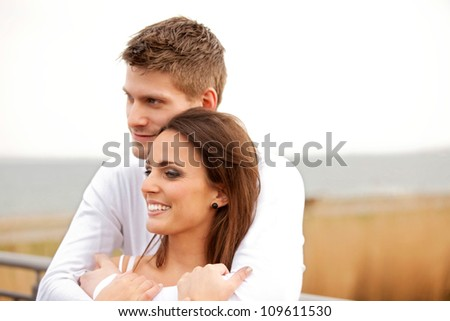 Closeup portrait of a cuddling couple outdoors in a park - stock photo