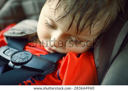 Closeup portrait of a cute adorable little boy toddler tired and sleeping belted in car seat on his trip, safety protection concept - stock photo