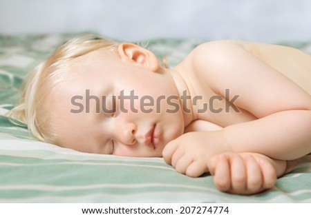 Closeup portrait of a cute adorable white blond Caucasian baby toddler sleeping dreaming, lying on a bed indoor - stock photo