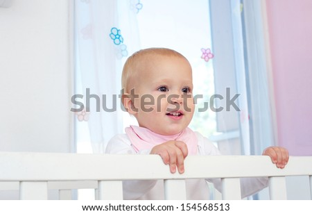 Closeup portrait of a cute baby smiling in crib
