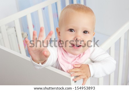 Closeup portrait of a cute baby waving hello and smiling from crib