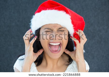 Closeup portrait of a cute Christmas woman with a red Santa Claus hat, white dress, screaming out loud, frustrated, eyes shut in rage. Negative human emotion on an isolated grey background. - stock photo