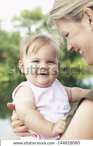 Closeup portrait of a cute daughter with smiling mother against the lake - stock photo