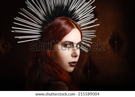 Closeup portrait of a cute gothic girl wearing spiked headgear - stock photo