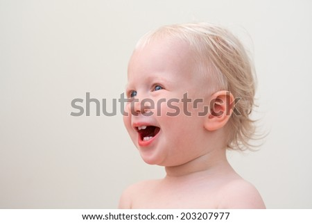 Closeup portrait of a cute laughing blond baby with blue eyes on a light background