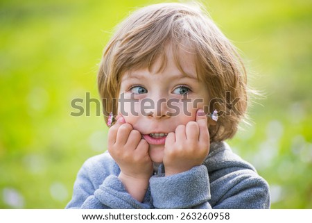 Closeup portrait of a cute little boy on light green background in spring park holding two daisies in the hand