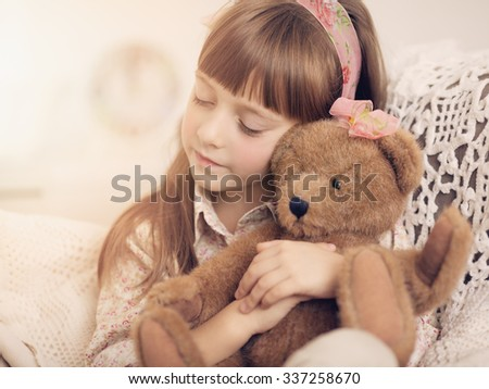Closeup portrait of a cute Little girl is daydreaming with her toy bear - stock photo