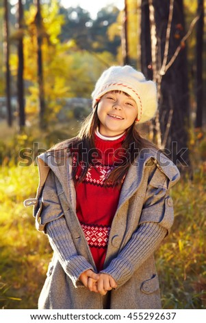 closeup portrait of a cute smiling little girl in a coat and beret in autumn