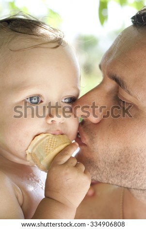 Closeup portrait of a daddy and his baby girl eating ice cream. Father gently kisses his little pretty daughter, enjoying parenthood. Family happiness and father's love concept. Colorful photo - stock photo