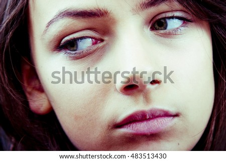 Closeup portrait of a distracted teenage girl, averting her eyes. Horizontal format.