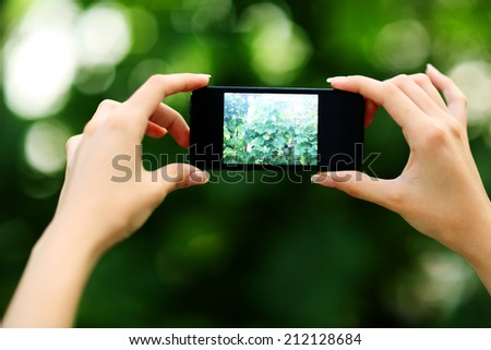 Closeup portrait of a female hands making photo with smartphone