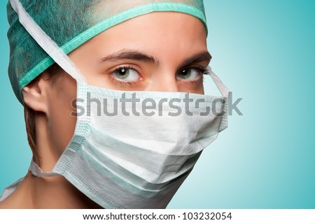 Closeup portrait of a female surgeon in a green background - stock photo