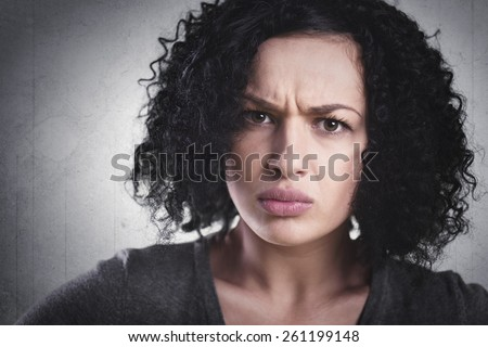 Closeup portrait of a frowning woman, being angry and mad, isolated on grey background. - stock photo