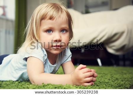 closeup portrait of a funny little girl. child playing at home - stock photo