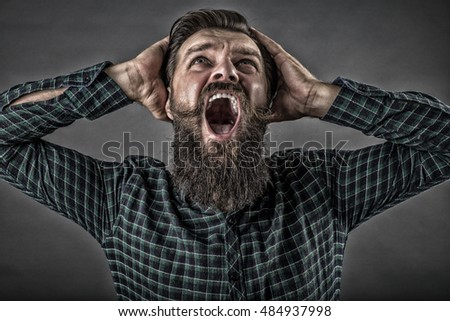 Closeup portrait of a furious young man yelling over gray background