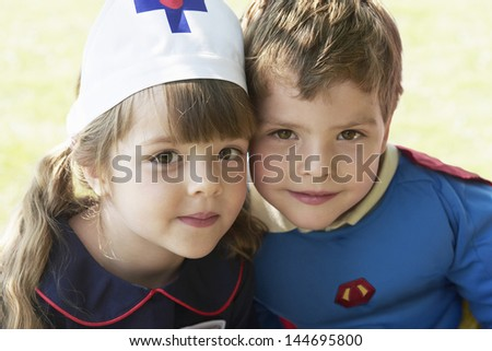 Closeup portrait of a girl and boy dressed up as nurse and superhero in the park - stock photo