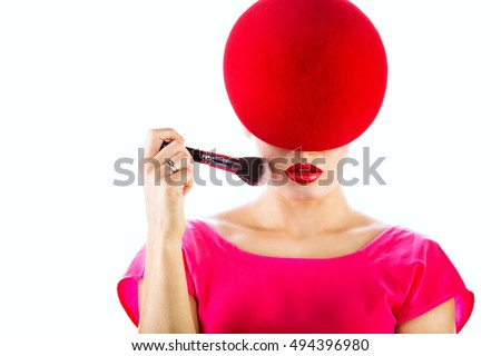 closeup portrait of a girl in a red hat holding a brush in his hand
