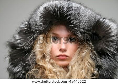 Closeup portrait of a girl in fir coat - stock photo