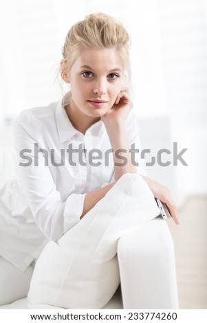 closeup portrait of a gorgeous blond young woman sitting in a white couch, looking at camera - stock photo