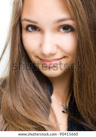 Closeup portrait of a gorgeous young brunette model girl with cute smile.