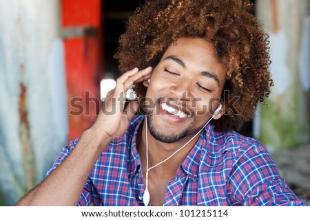 closeup portrait of a handsome African American man at the beach listening to music - stock photo