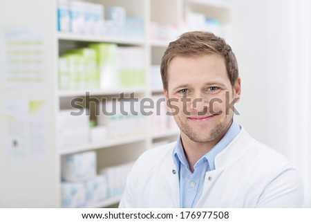 Closeup portrait of a handsome pharmacist with a beaming smile standing in his pharmacy - stock photo