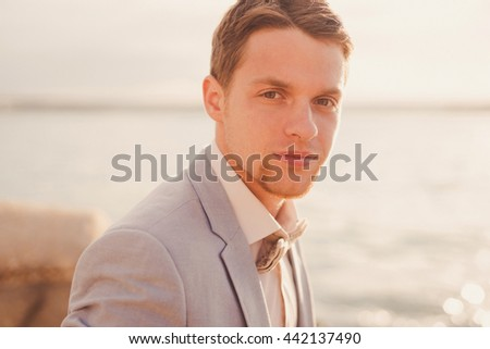 Closeup portrait of a handsome young caucasian stylish man with beard on the background of beautiful nature, sea in sunlight - stock photo