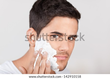 Closeup portrait of a handsome young Latino man applying shaving cream to his face - stock photo