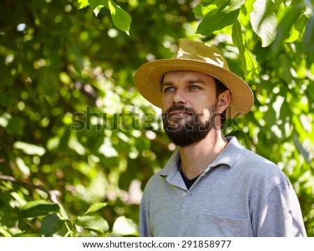 Closeup portrait of a hansome bearded young farmer outdoor