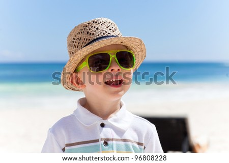 Closeup portrait of a happy boy in a straw hat on a tropical beach - stock photo