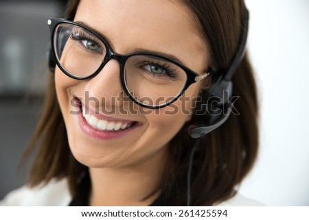 Closeup portrait of a happy female support operator in headset - stock photo