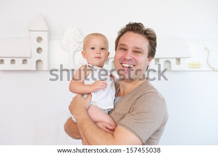 Closeup portrait of a happy man smiling and holding cute baby - stock photo